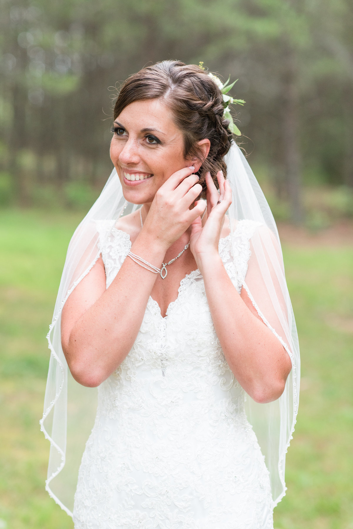 a bride wearing a laced thin strapped wedding dress fixing her earrings while looking off at Meadows at Walnut Cove
