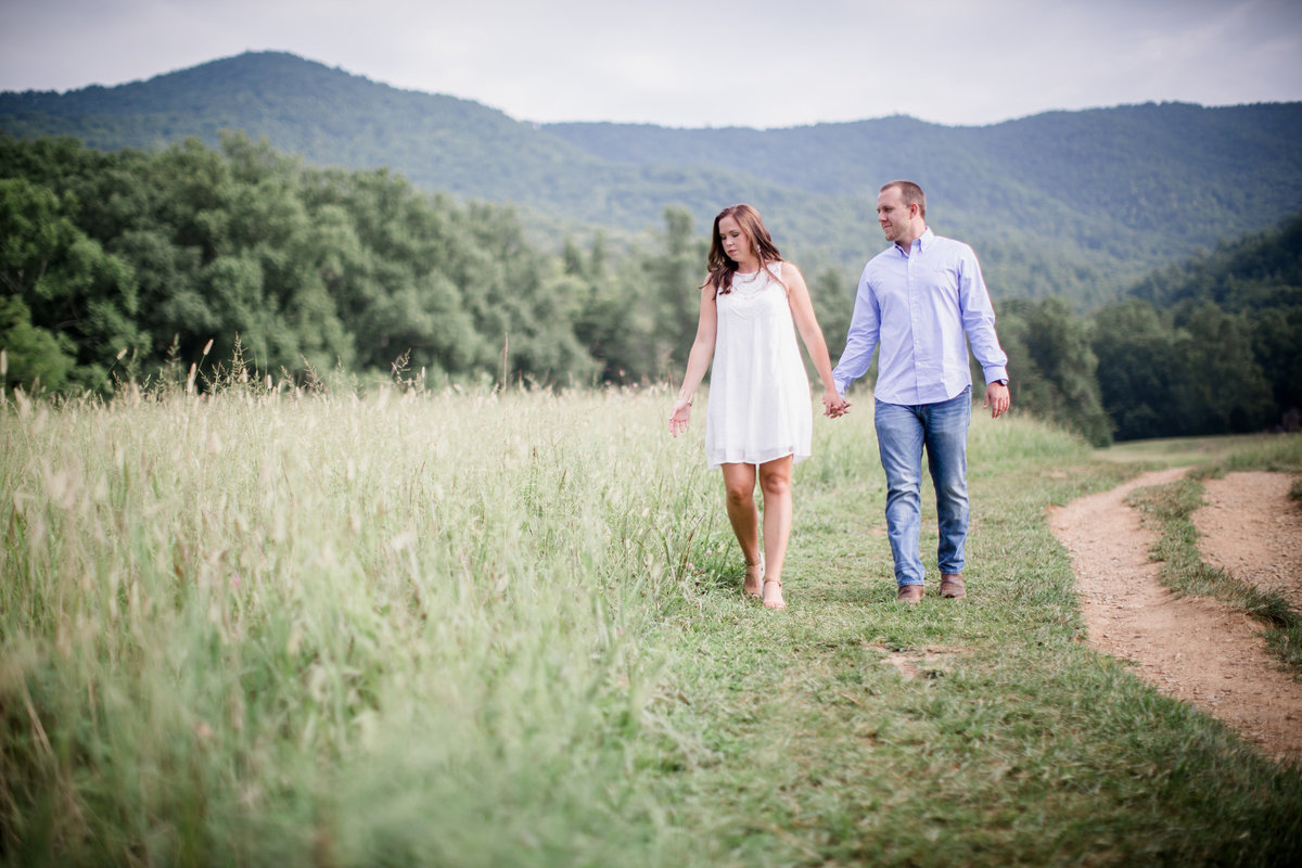 Walking with her hand brushing the tall grass in Cades Cove engagement photo by Knoxville Wedding Photographer, Amanda May Photos.