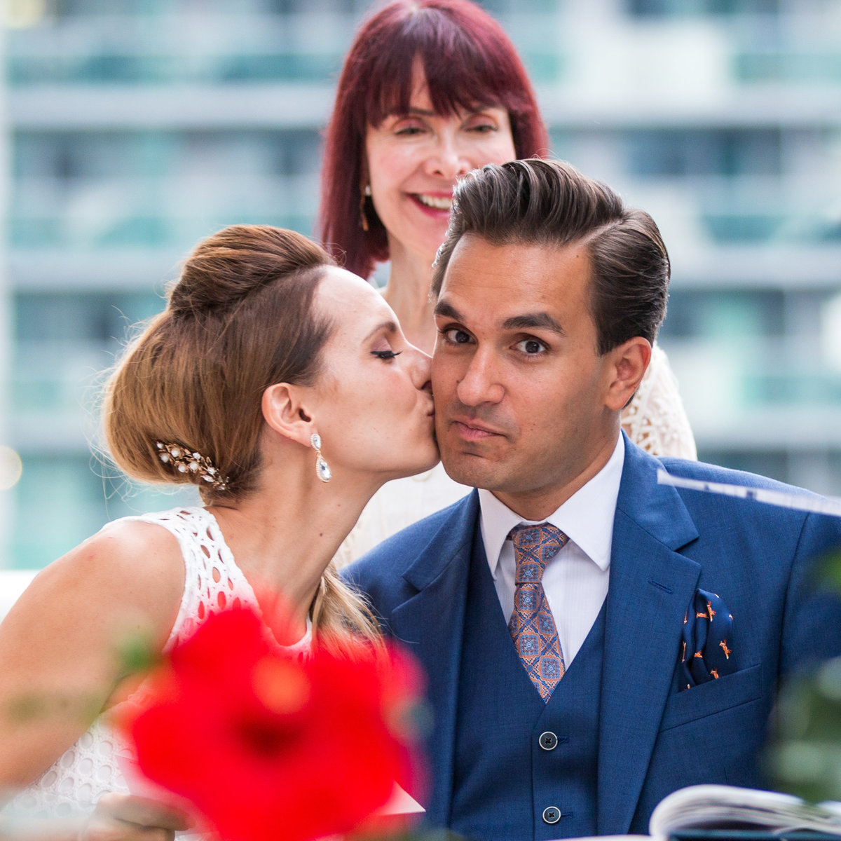 A bride kisses her groom with a red flower in the forground that is out of focus while the focus is on their faces