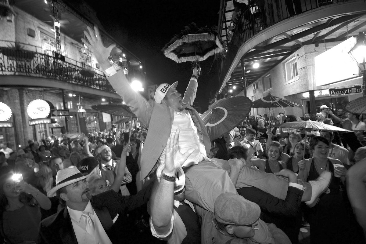 a groom celebrates his wedding on Bourbon Street during wedding second line parade