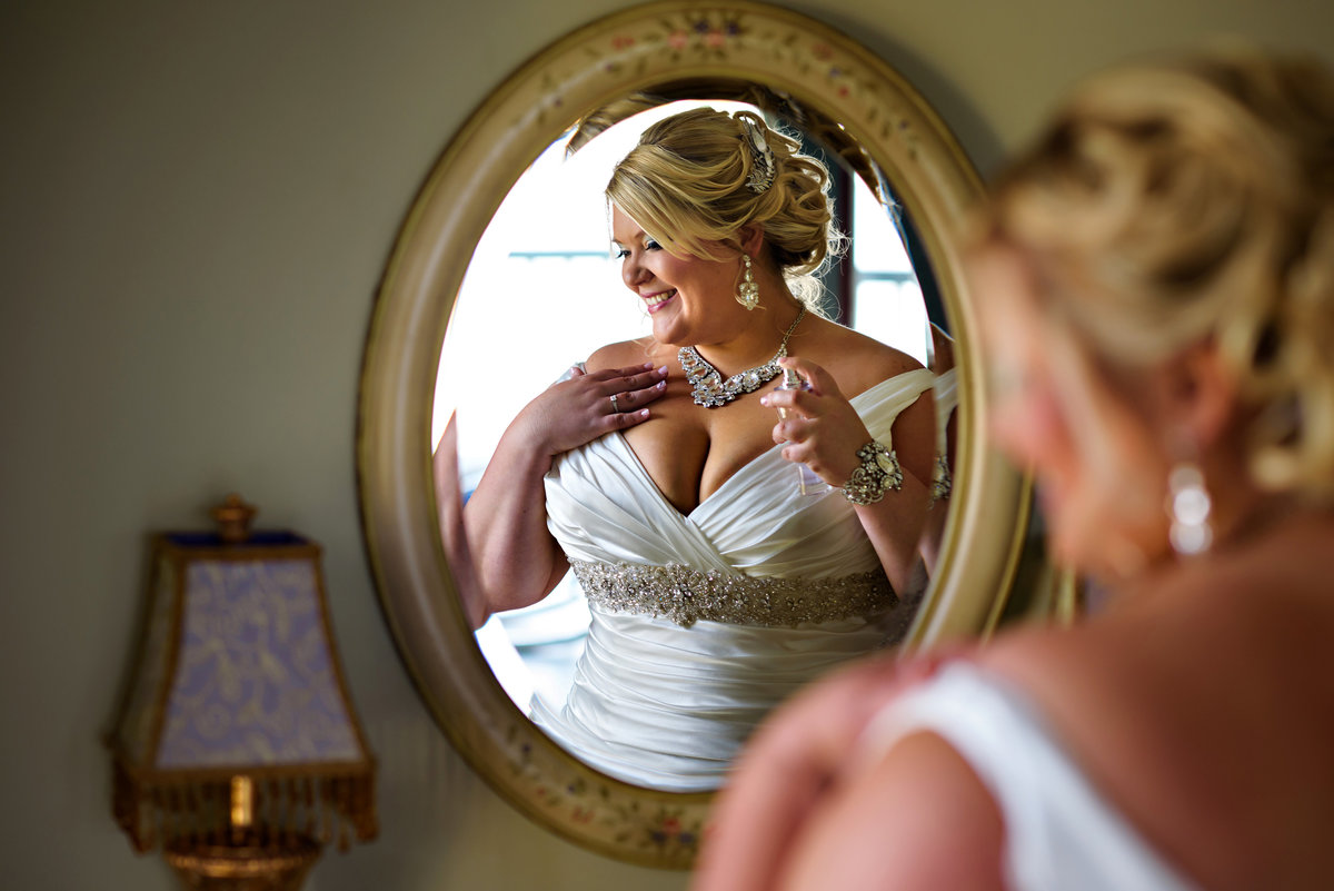 A beautiful bride applies her perfume in the mirror before her ceremony.