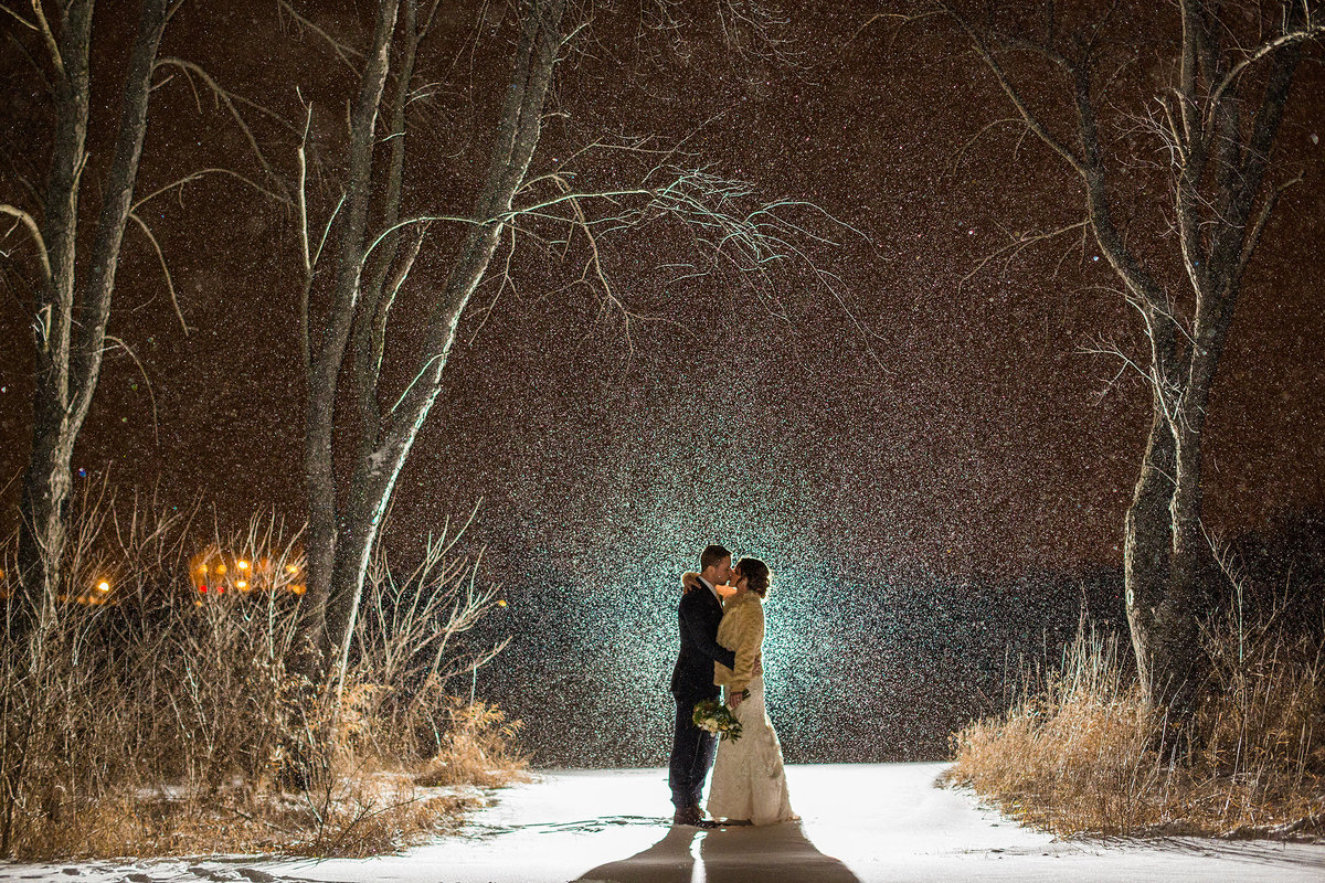 bride and groom kissing during a snowy wedding