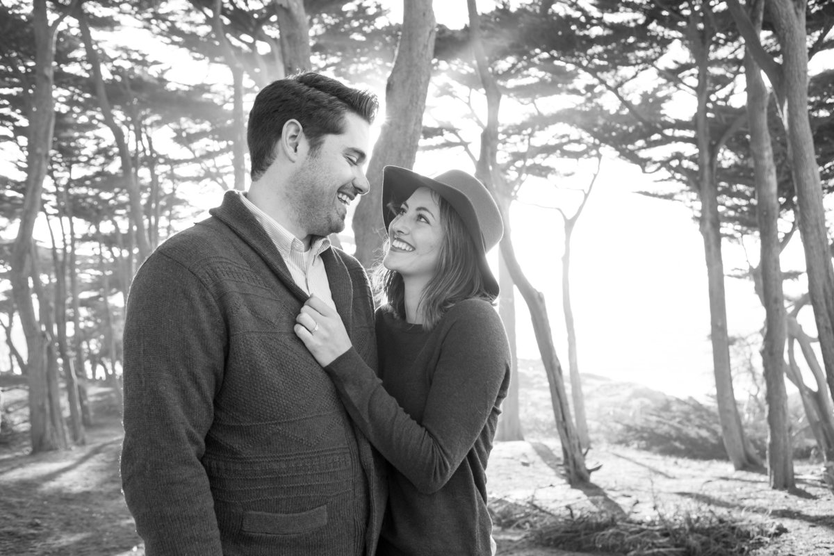 engaged couple give each other happy looks at lands end before sunset in san francisco