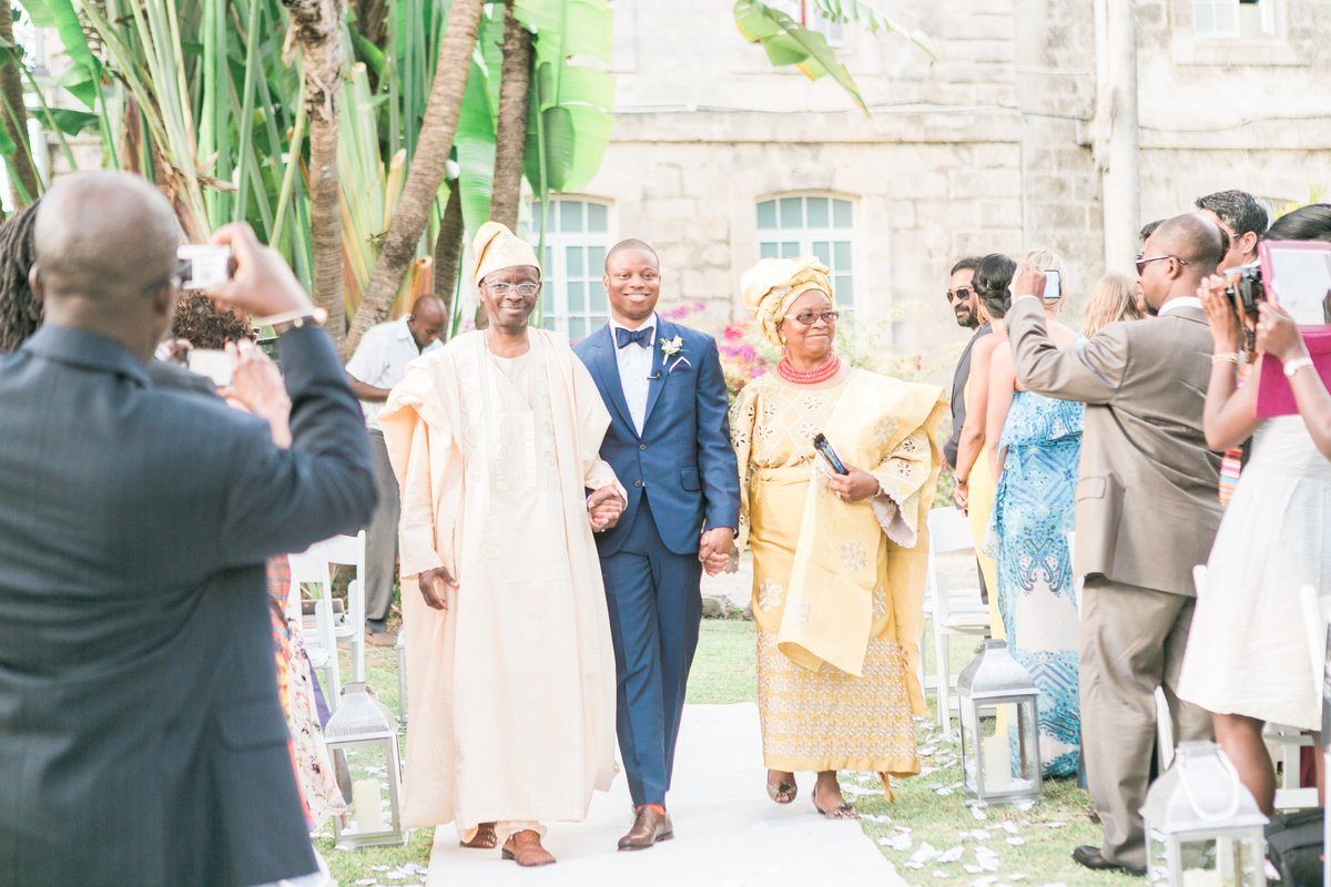 Groom walking down wedding aisle in Barbados, Codrington College, with parents in tradition dress from Ghana | International wedding ceremony