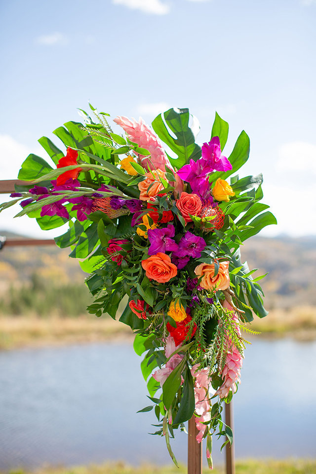 granby-colorado-Strawberry-Creek-Ranch-Wedding-Ashley-McKenzie-Photography-tropic-meets-mountain-wedding-colorful-arbor-with-tropical-leaves