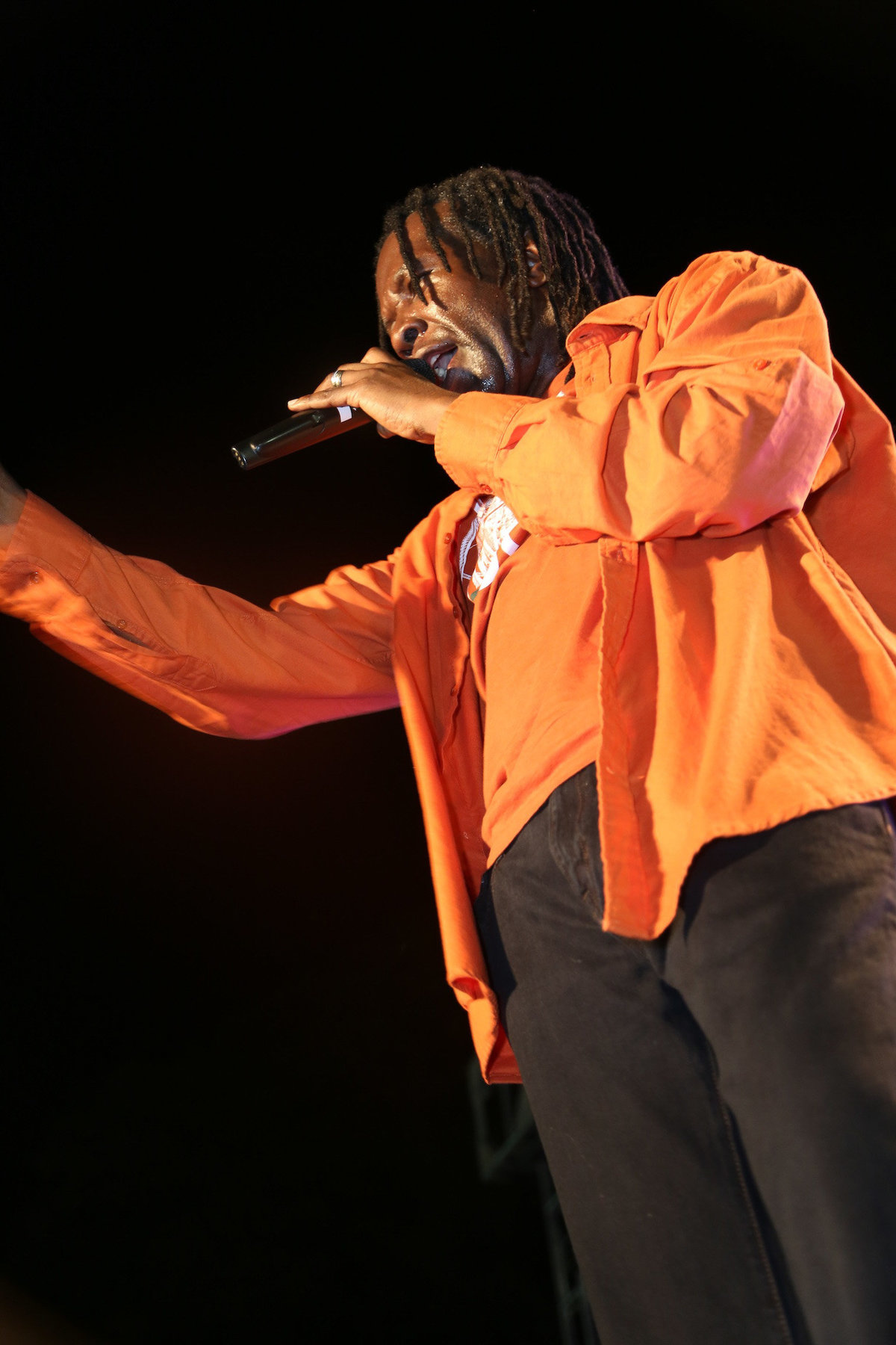 A portrait of international singer David Rudder wearing an orange shirt  while performing on stage. Photo by Ross Photography, Trinidad, W.I..