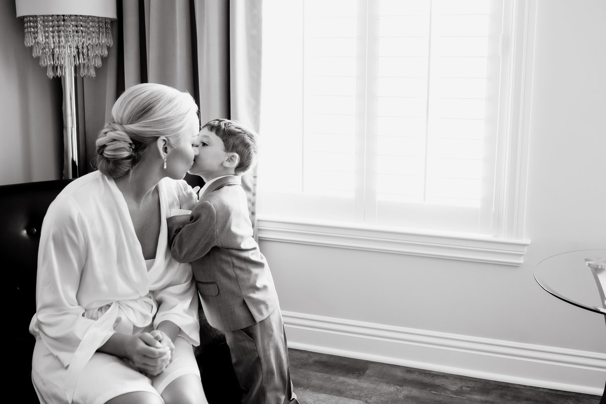 Black and white photo of bride being kissed by little boy prior to ceremony