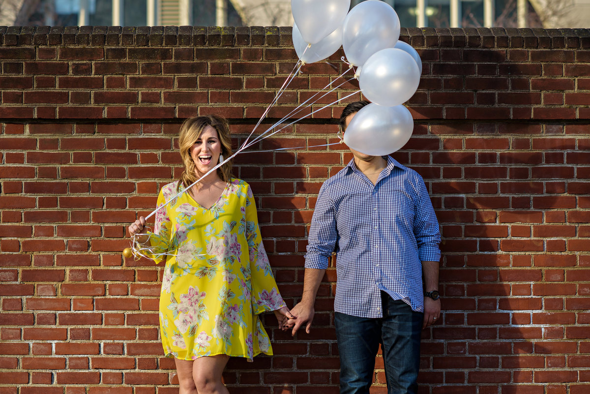 A pregnant mother holds balloons during a maternity session and the wind blows them in front of her husband's face.