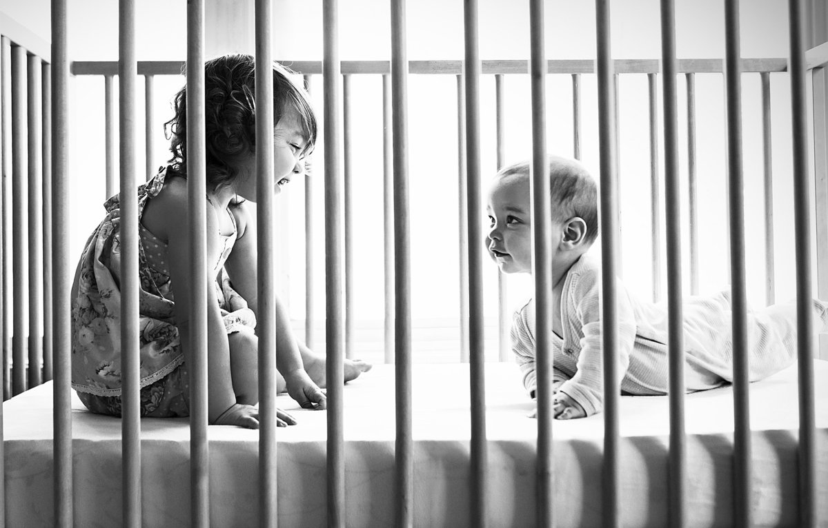 charlotte documentary photographer jamie lucido captures a beautiful candid image of children playing in their crib
