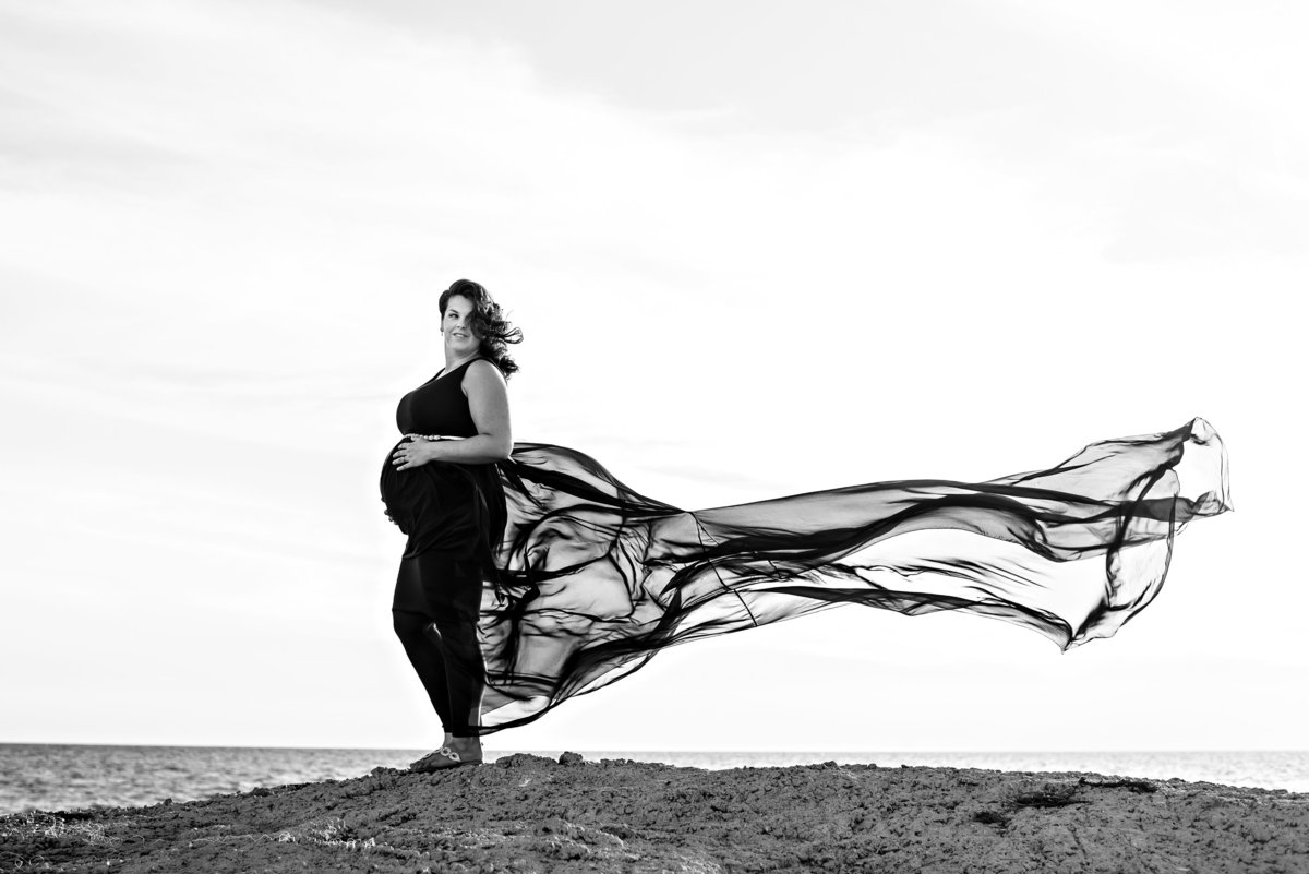 A mother to be holds her pregnant belly and her dress blows in the wind at the beach.