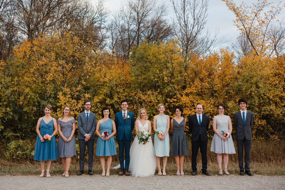 Bridal party poses for a group photo in the fall