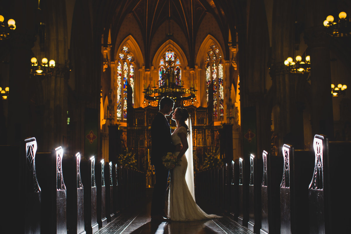 a silhouette of the bride and groom taken down the aisle in a manchester church