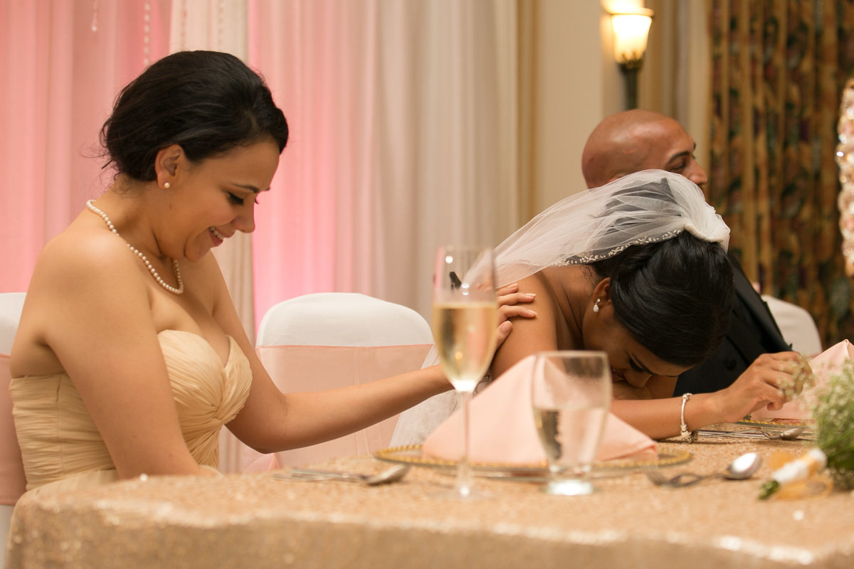 Bride and bridesmaid laugh at reception. Photo by Ross Photography, Trinidad, W.I..