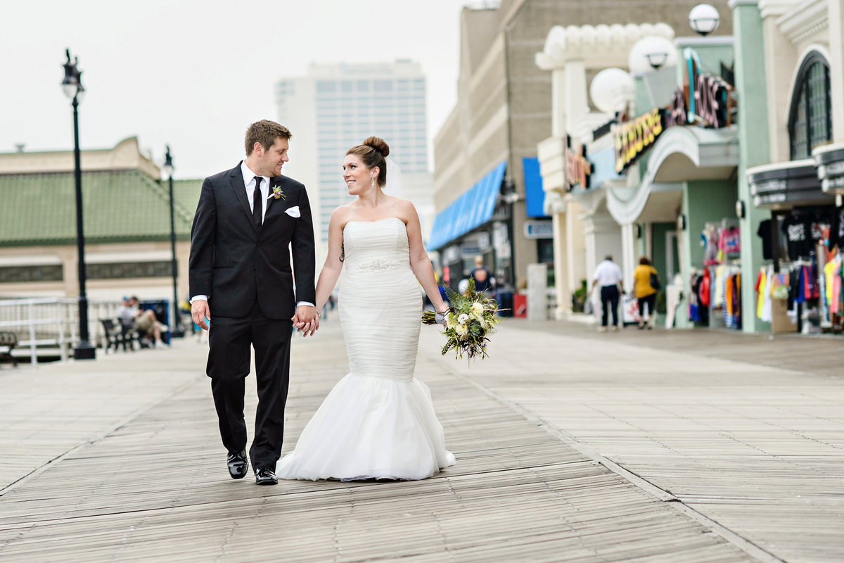 A bride and groom walk along the boardwalk outside their Chelsea Hotel Wedding.