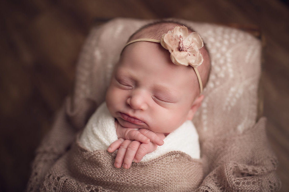 Baby wrapped with headband in pink blanket on wood backdrop