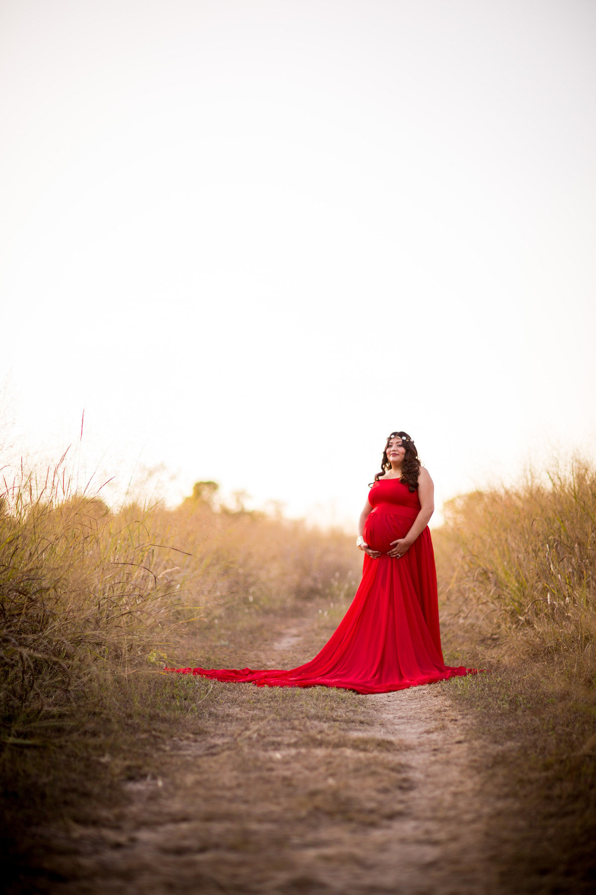 San Antonio Maternity photography session of woman in red maternity dress standing in field at Cibolo Nature Center.