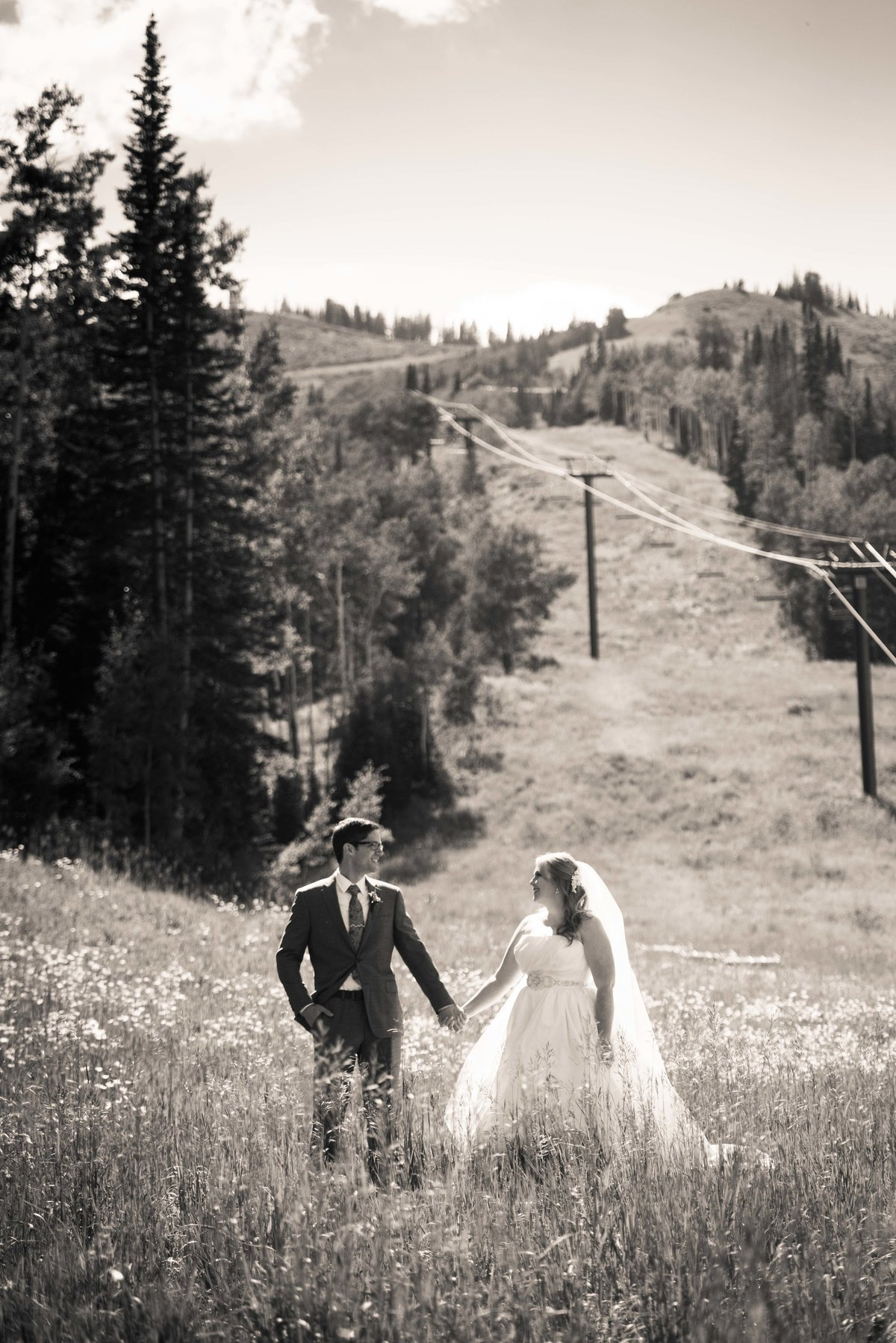 Bride and groom pose at foot of mountain, Park City.