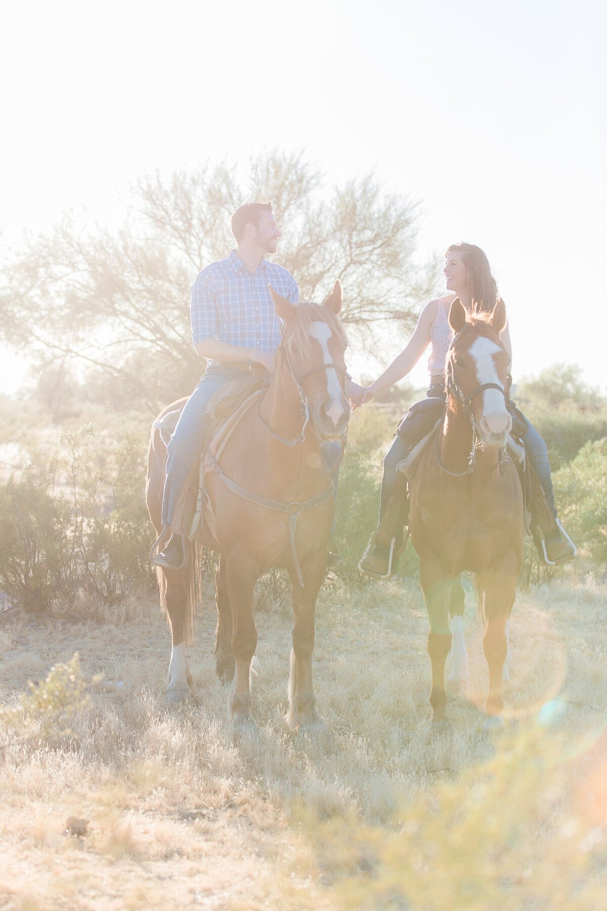couple sitting on their horses next to each other while holding hands and looking at each other.
