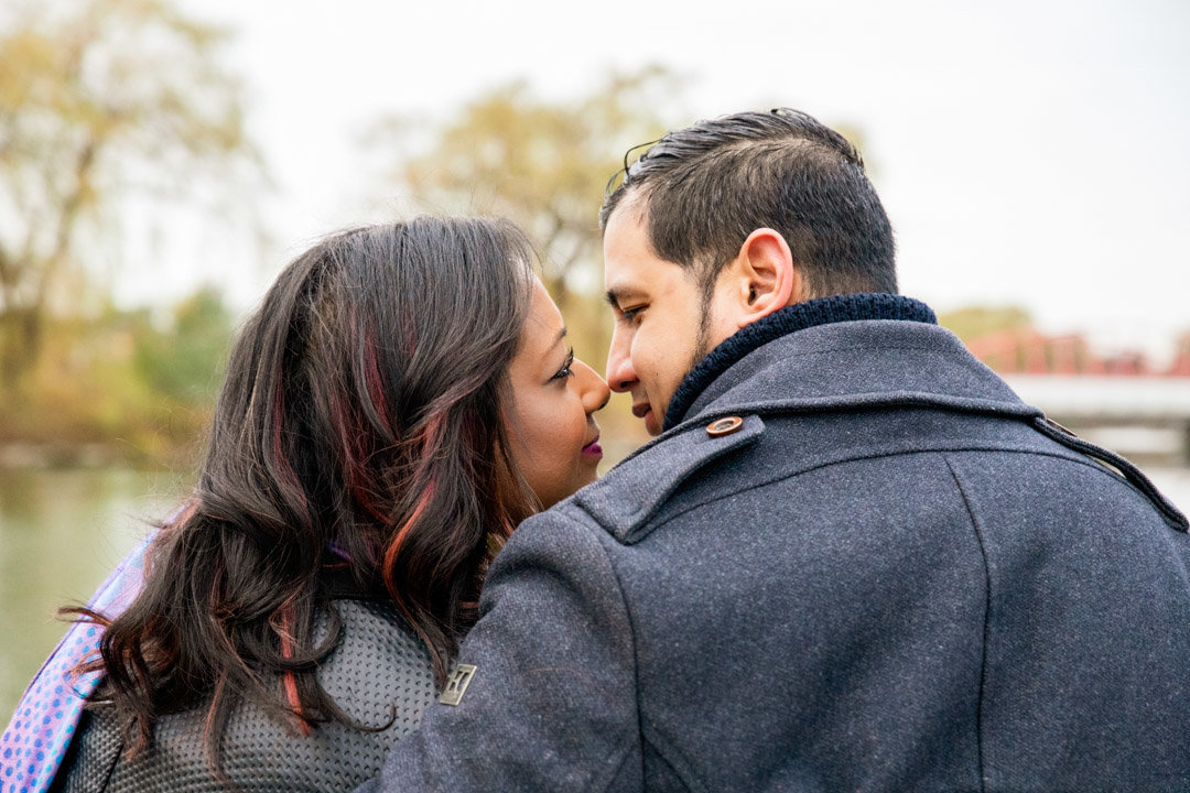 The back of a couple as they are about to kiss in front of the pond at Chinguacousy Park Brampton
