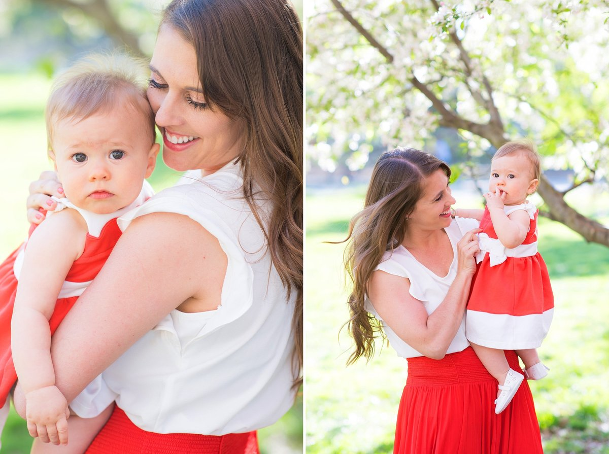 Mother and baby girl smiling in red dresses under spring cherry blossom tree in Hudson River Greenway in New York City Photo
