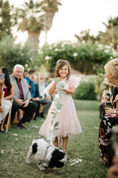 flower girl walking a dog down the aisle
