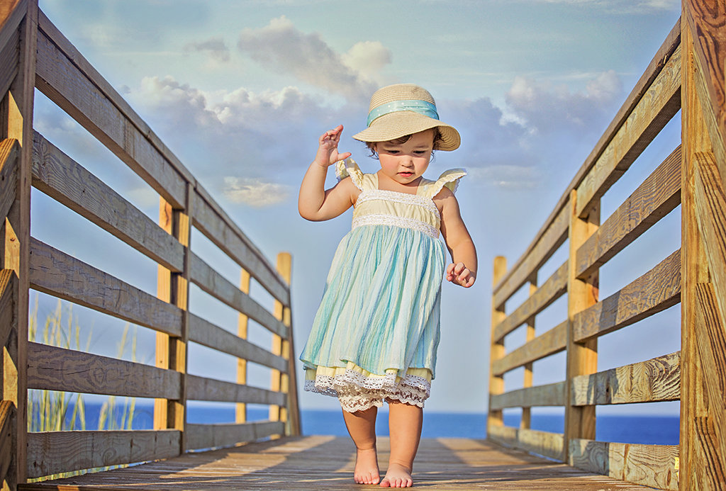 Charlotte family photographer Jamie Lucido captures a beautiful image of a young child walking on a boardwalk at OuterBanks North Carolina