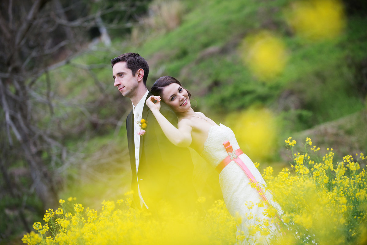 bride and groom pose in field of yellow flowers in valle crucis nc