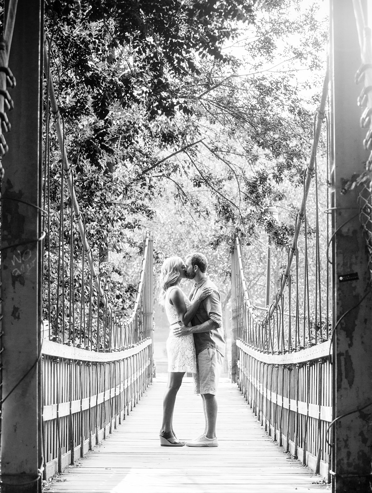 charlotte wedding photographer jamie lucido captures an engaged  couple embracing on a bridge at Freedom Park
