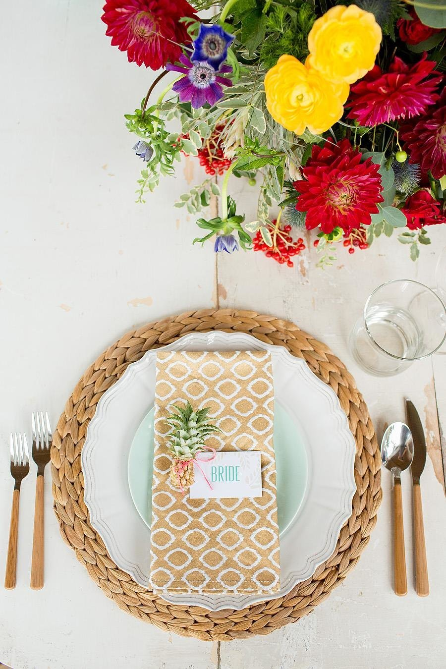 tropical table setting with mini pineapple and bright flowers