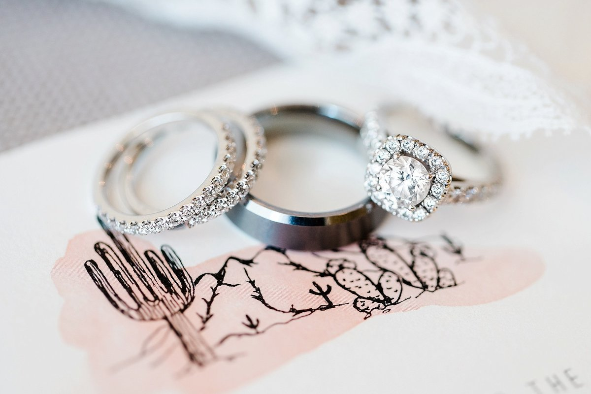 wedding rings detail photo with desert inspired wedding invitation