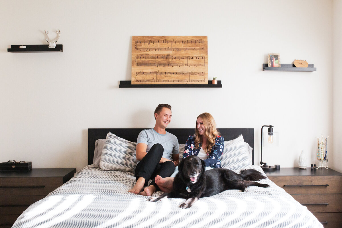 A young husband and wife sit on their bed with their big black lab.