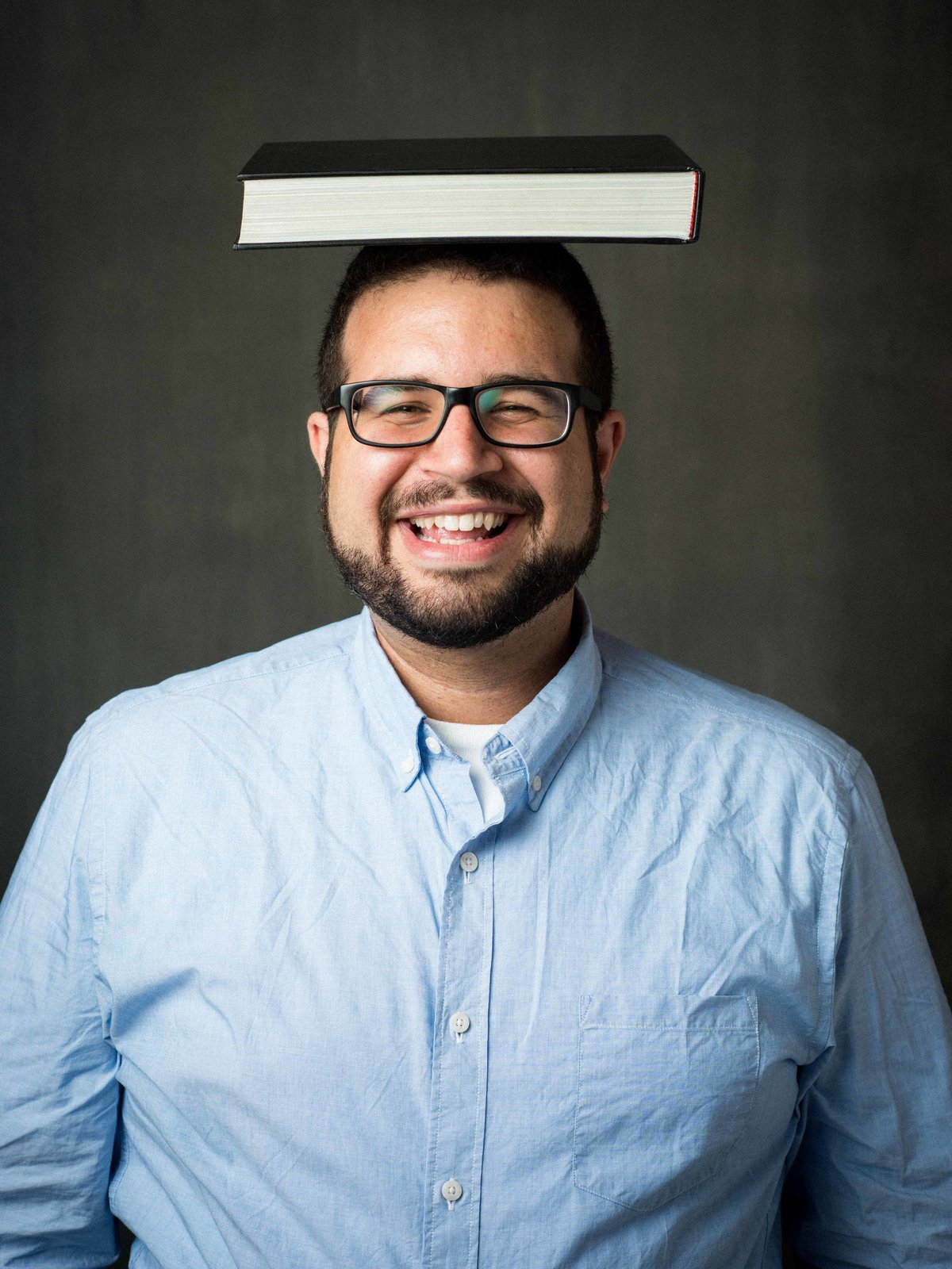 Studio portrait, man smiling with book on head. Chicago.