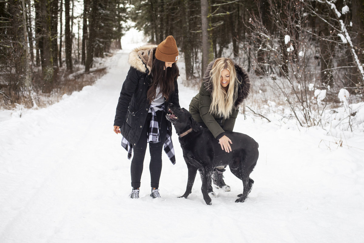 two girls in the snow with dog
