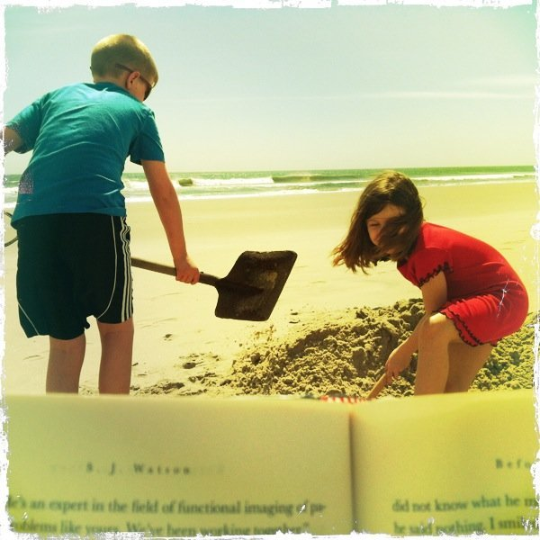 On the beach with a book and my kids