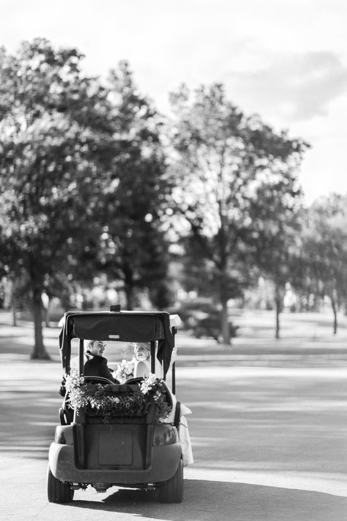 Bride and groom riding golf cart at Hartford Country Club