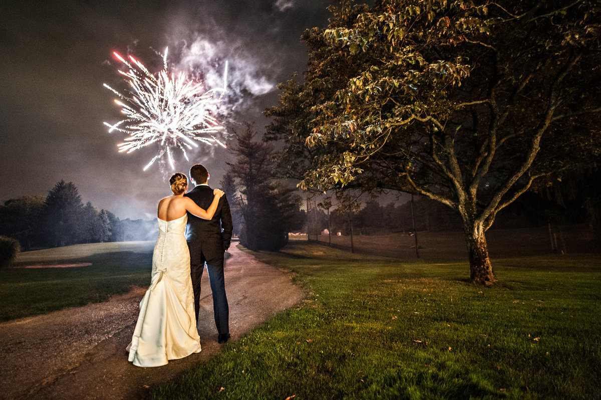 A bride and groom enjoy a firework show at their wedding at Penn Oaks Golf Club.