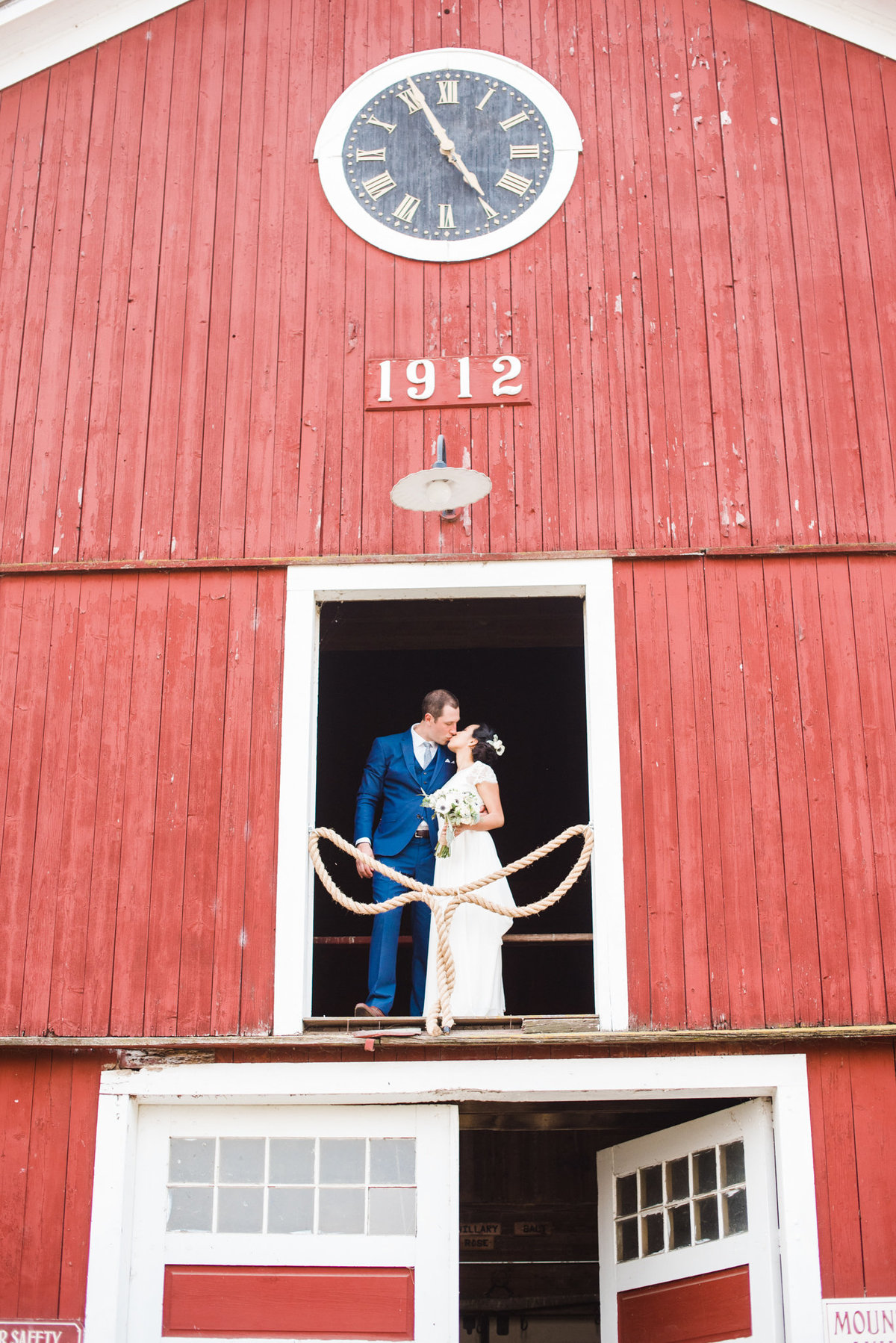 bride and groom in barn clock tower