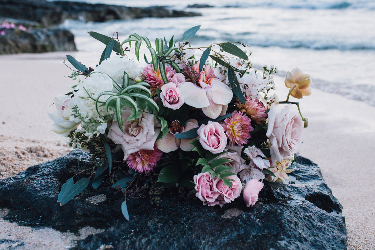 Bridal bouquet resting on rock by the ocean after elopement