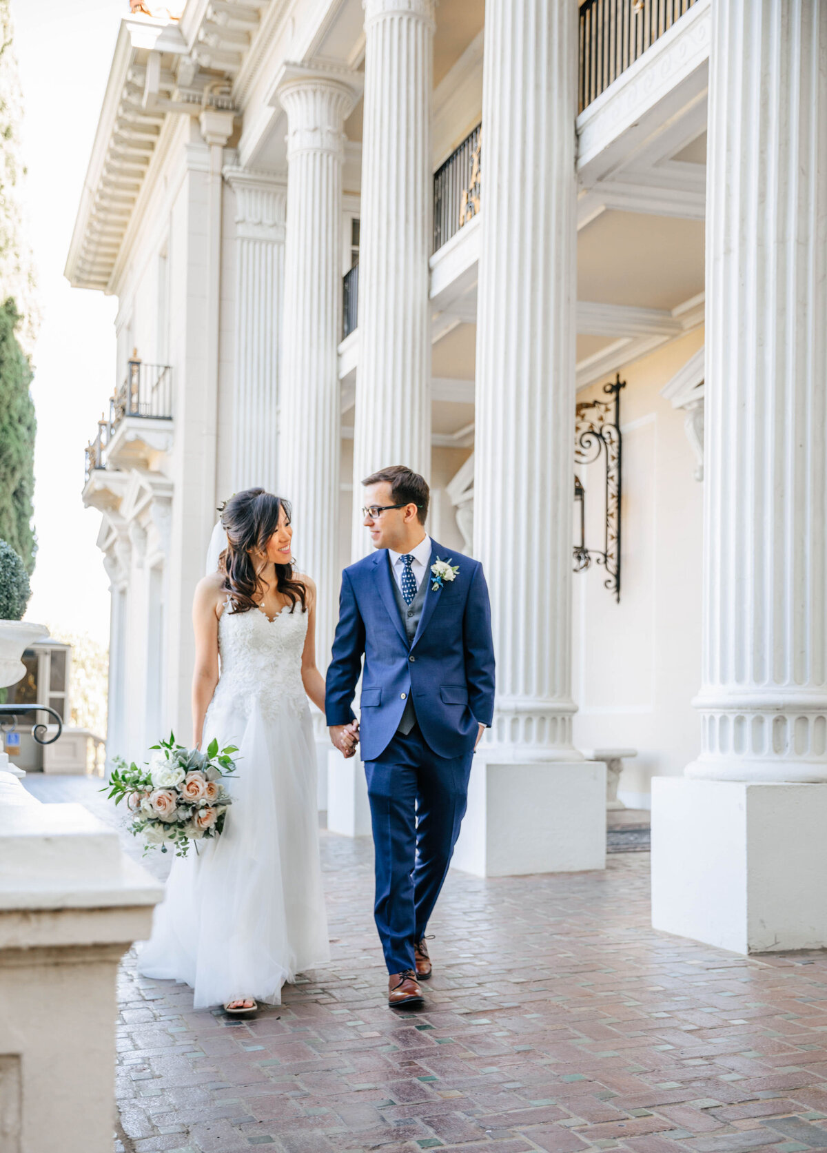 bride and groom walking in front of columns