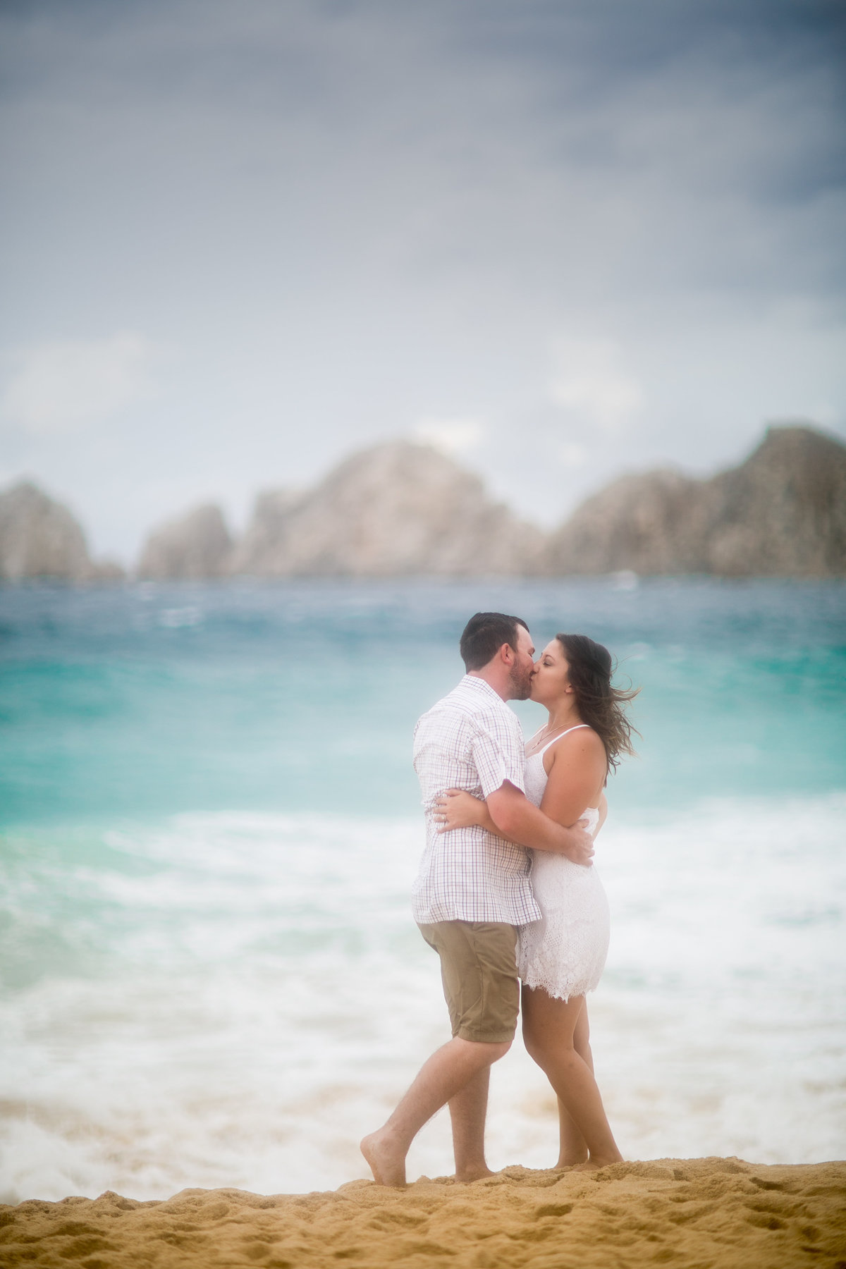 couple kissing on the beach in cabo san lucas