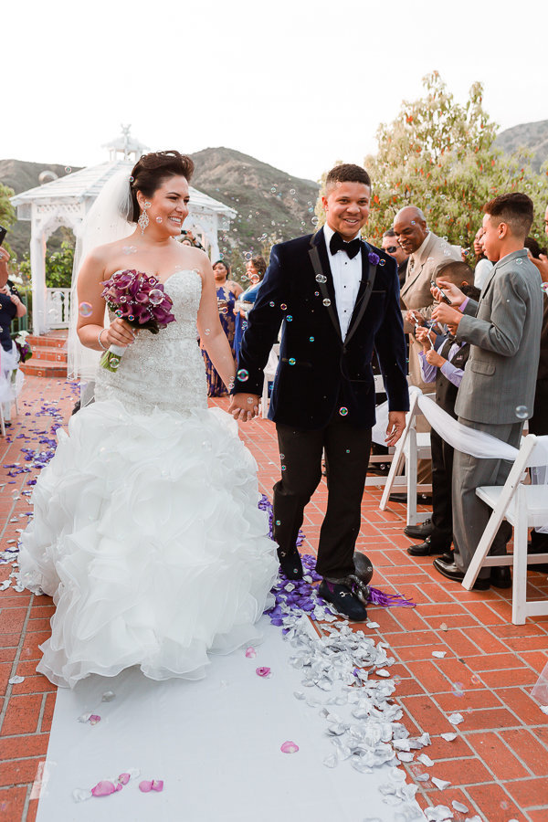 Bride and groom surrounded by bubbles walking down the isle after vows