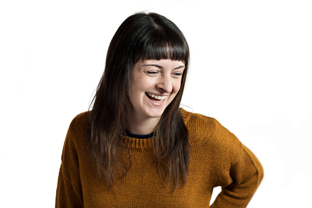 A headshot of a woman laughing for her social media websites.