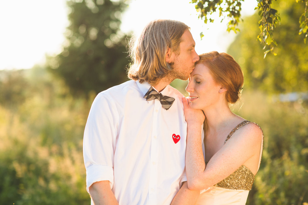 alternative bride and groom kissing forehead in golden hour