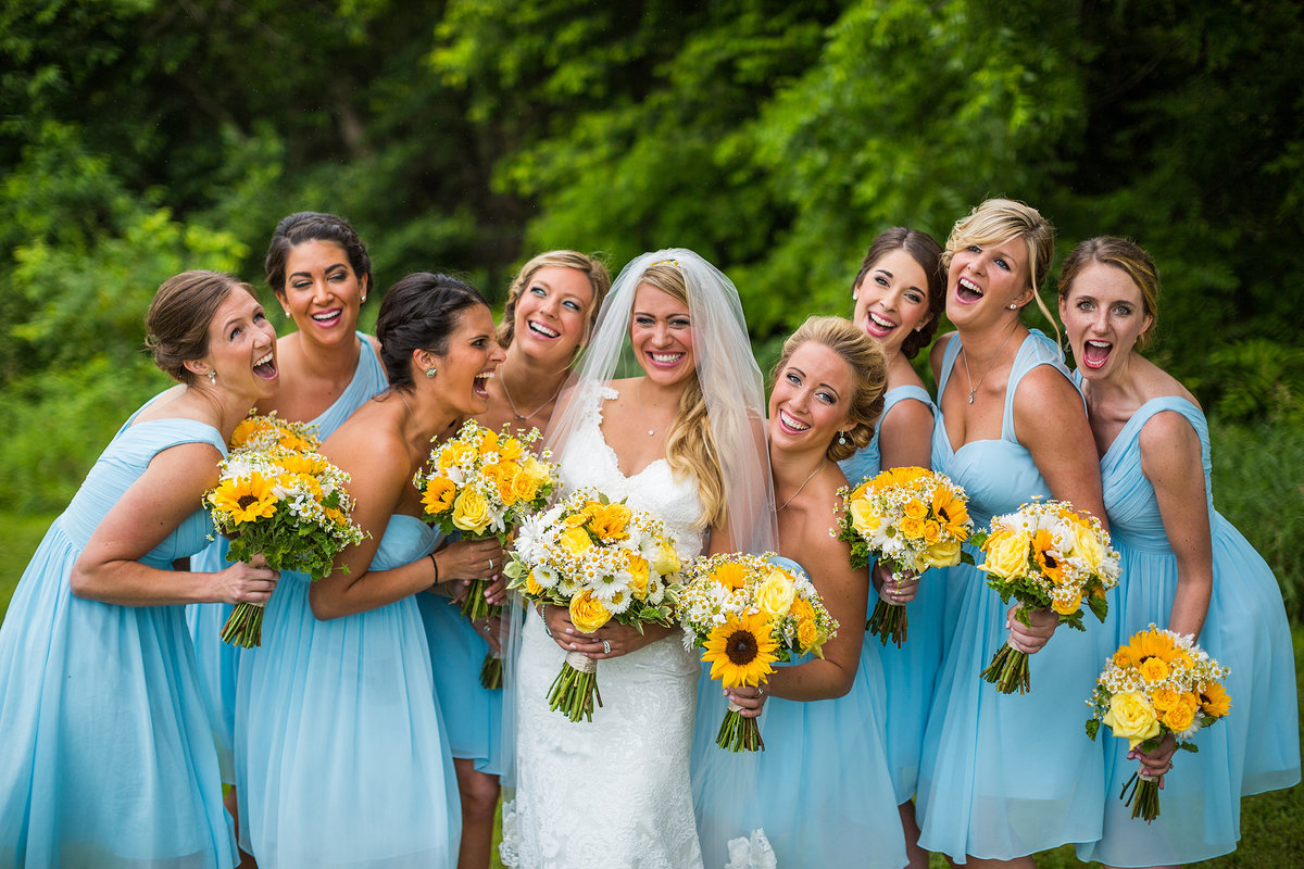 bride and bridesmaids with sunflowers and light blue dresses