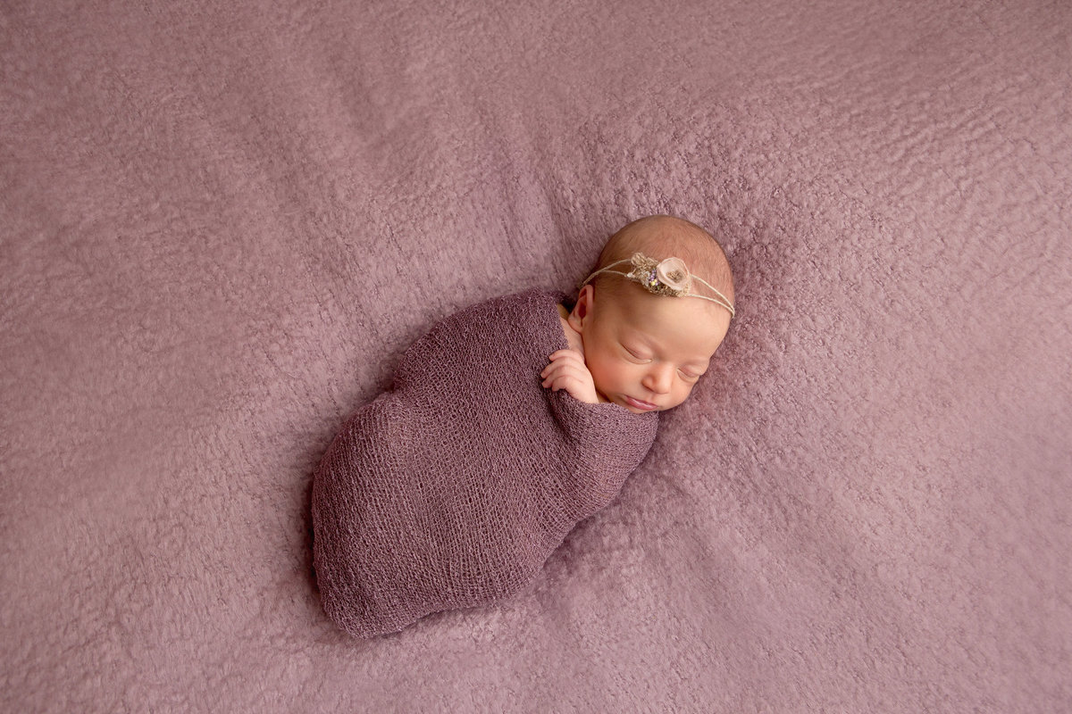 Pictures of sleeping posed newborn baby girl on fuzzy blanket with wrap and vintage inspired simple flower headband in Cornwall NY photo studio by Hudson Valley professional photographer Autumn Photography