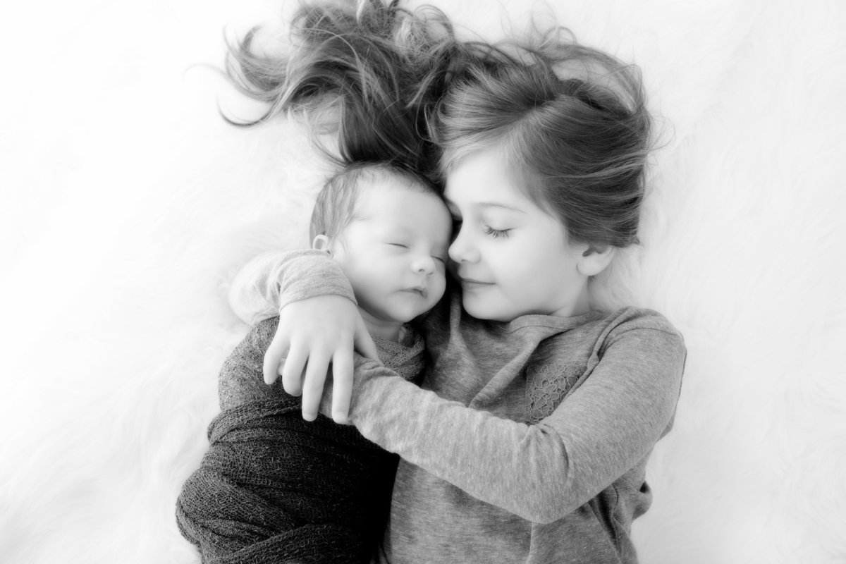 Black and white photo of big sister holding her baby brother as they are laying on the floor.  Baby is cradled in her arms as they lie on their backs