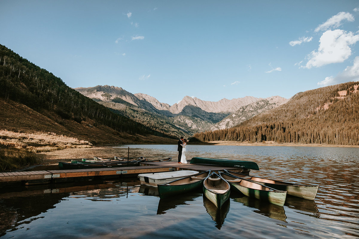 couple kissing on the dock in front of the Gore Range at Piney River Ranch in Vail, CO