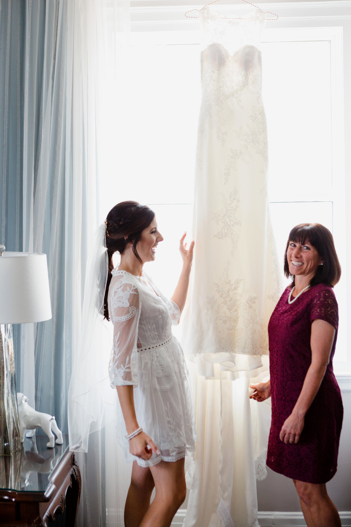 Mother of the bride and bride looking at wedding dress