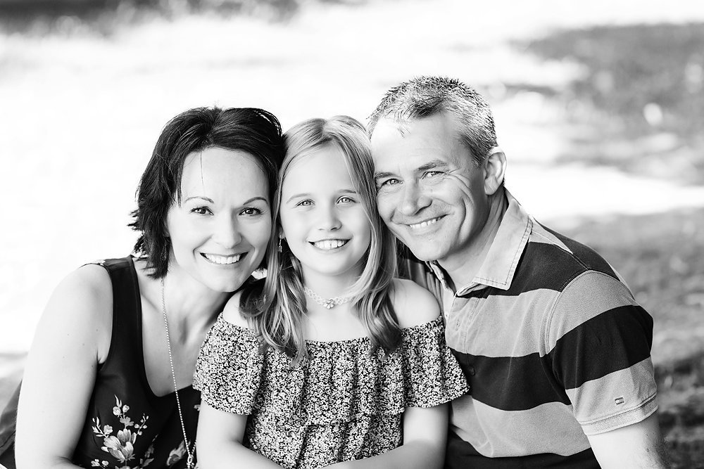 mum dad and daughter portrait in park