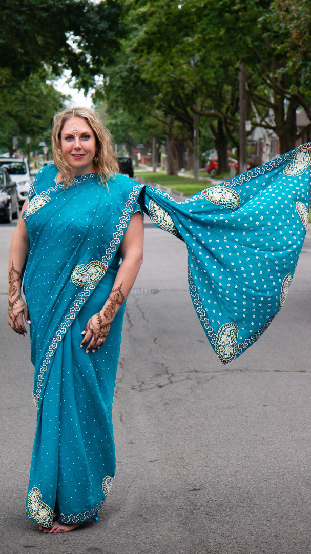 bride wearing a blue sari with silver embellishments and henna on arms with her dupatta flowing in the wind while she stands on the road
